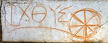 Ichthus word in Greek with a spoked wheel next to it scrawled in a orange color on stone.