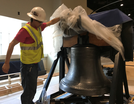 A worker unveils a liberty bell