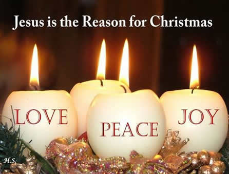 Three candles with the words Love Joy and Peace written on them.