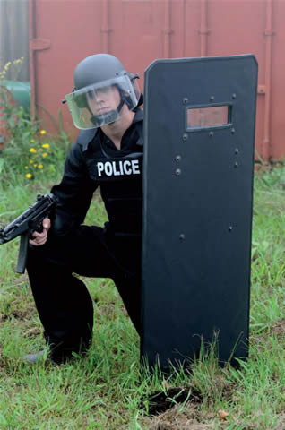 Picture of a police riot shield with a kneeling officer behind it