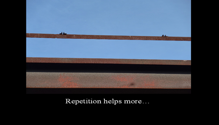 A black framed photo with the photo pulled further back so it looks like a possible overpass tressle with the words Repetition helps some written on the black frame
