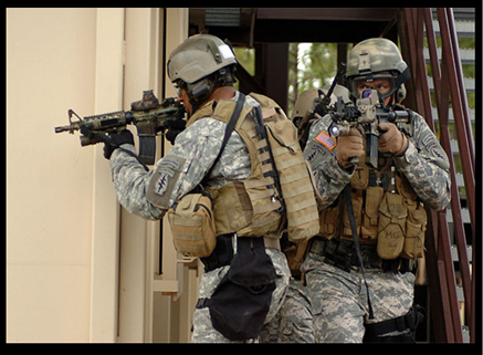 Picture of soldiers training weapons up as they move through rooms.